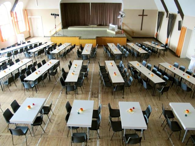 Großer Saal mit Tischen und Stühlen
